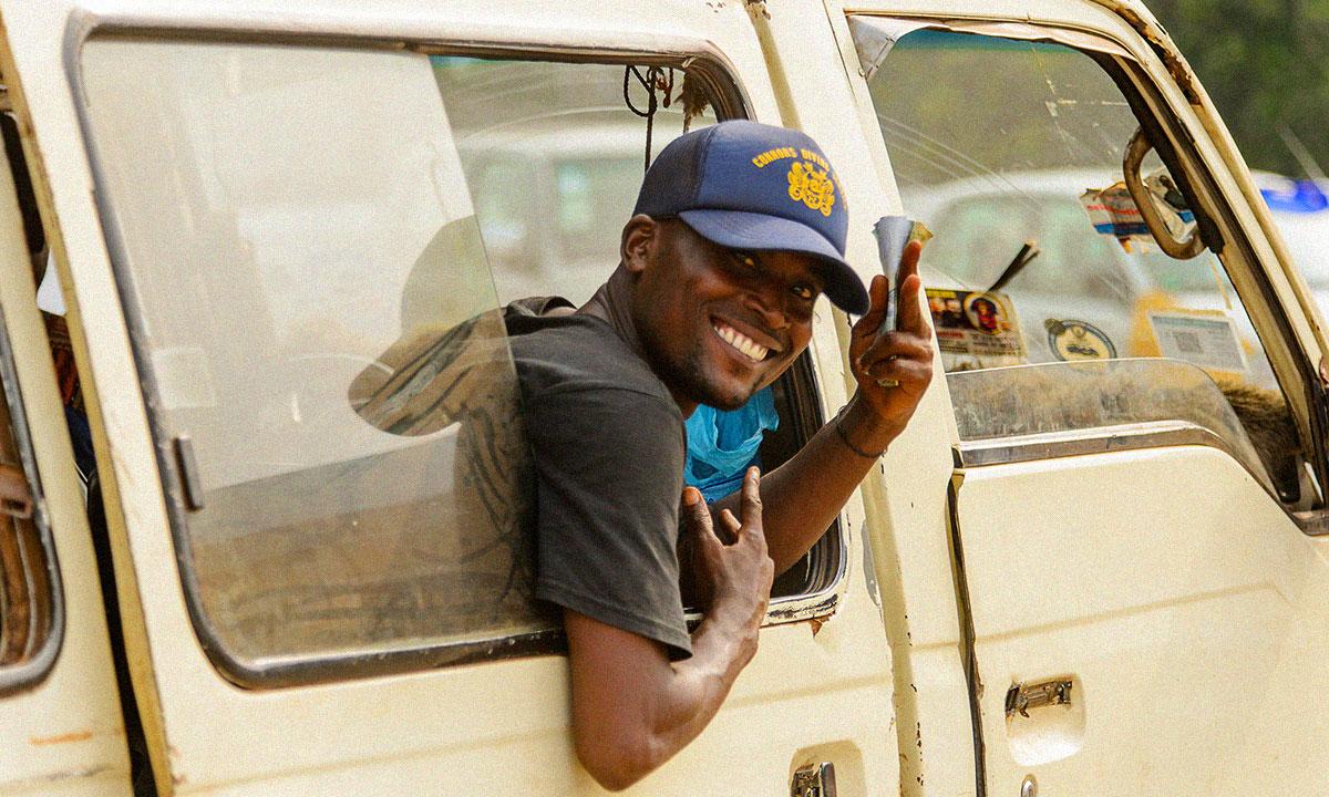 Ghanian man hangs out of a van in Accra